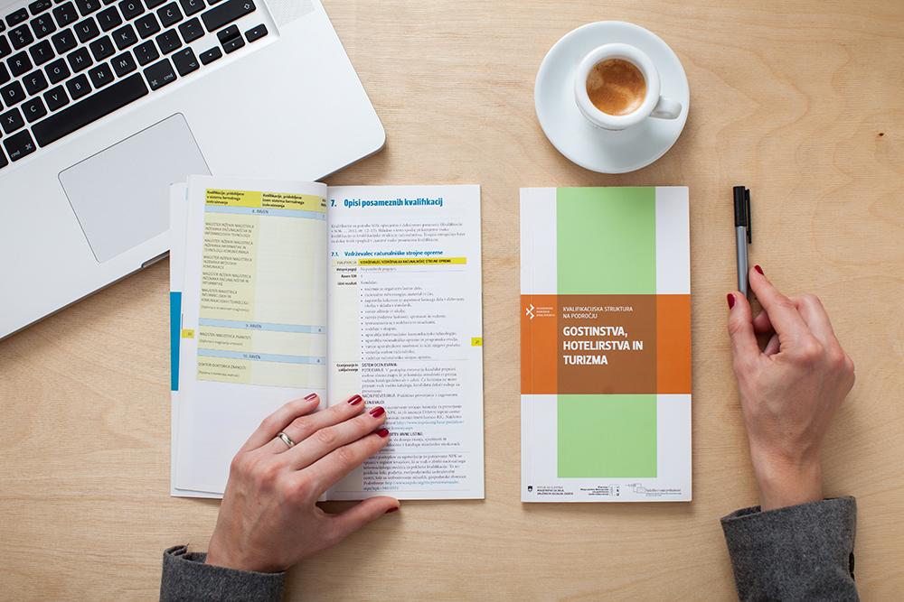 Uporabnik bere brošuro SOK ob kavi