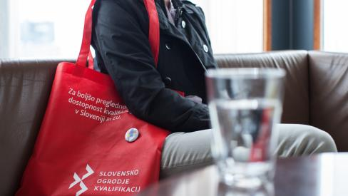 Woman sitting on a sofa with a red SQF promotional bag in front of a glass of water.