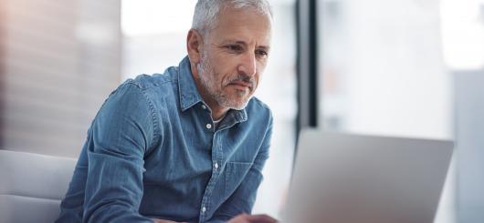 Slika moškega, ki uporablja prenosni računalnik.