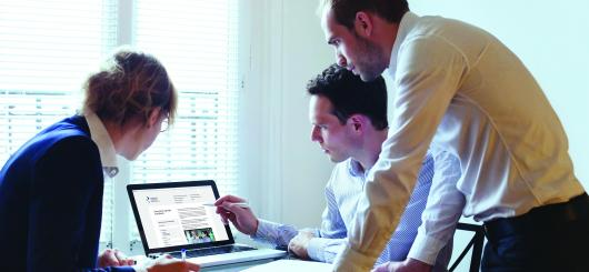 Three people working together and looking at a computer screen.